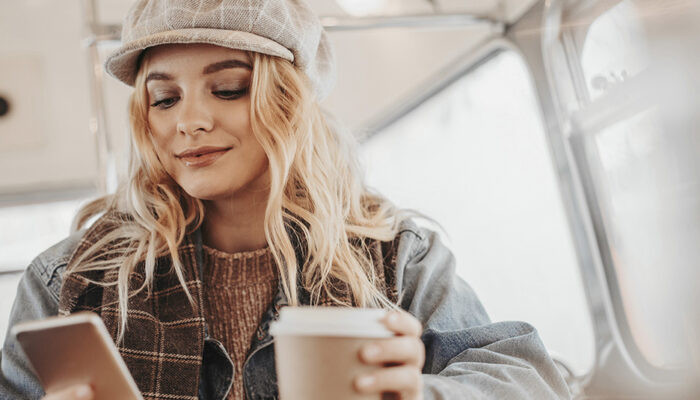 Lady with coffee using phone